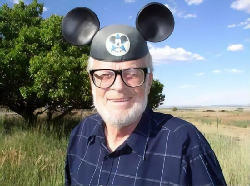 Dave wears Mickey Mouse ears while standing in an open expanse.