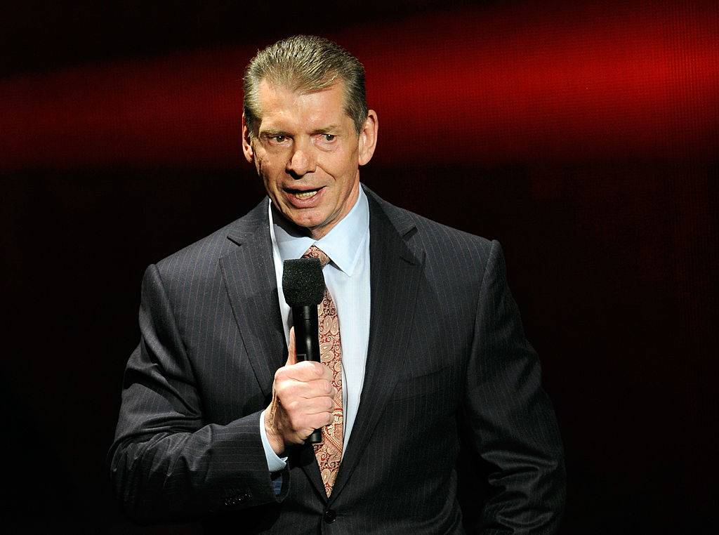 vince mcmahon holding a microphone